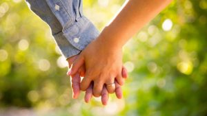 man and woman holding hands engaged